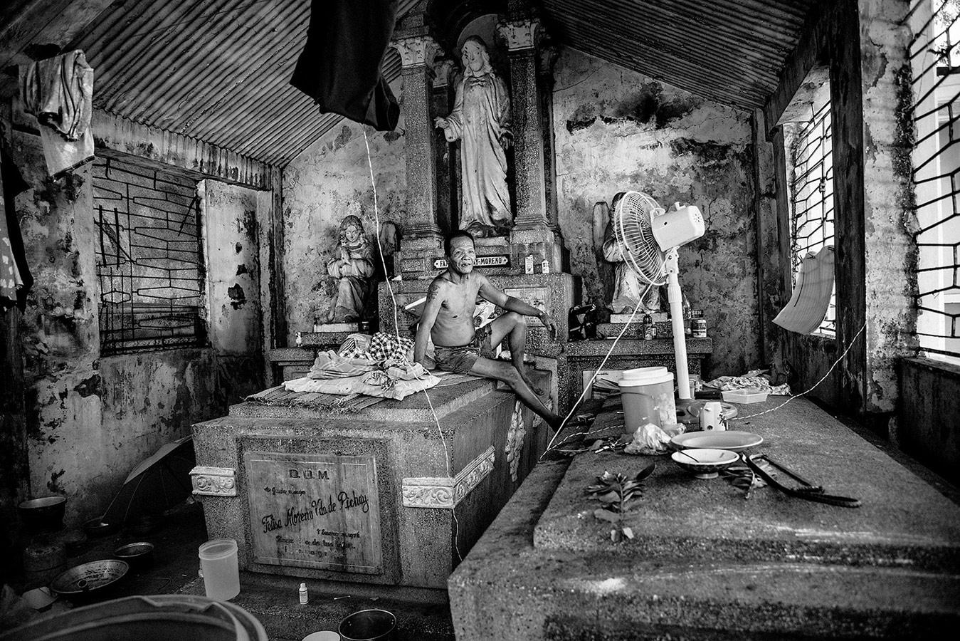 Рубен, 62 года, сидит на своей кровати в одном пантеоне на северном кладбище Манилы, где он живет уже 30 лет, © Бруно Галлардо, Испания, Конкурс портретной фотографии Kuala Lumpur