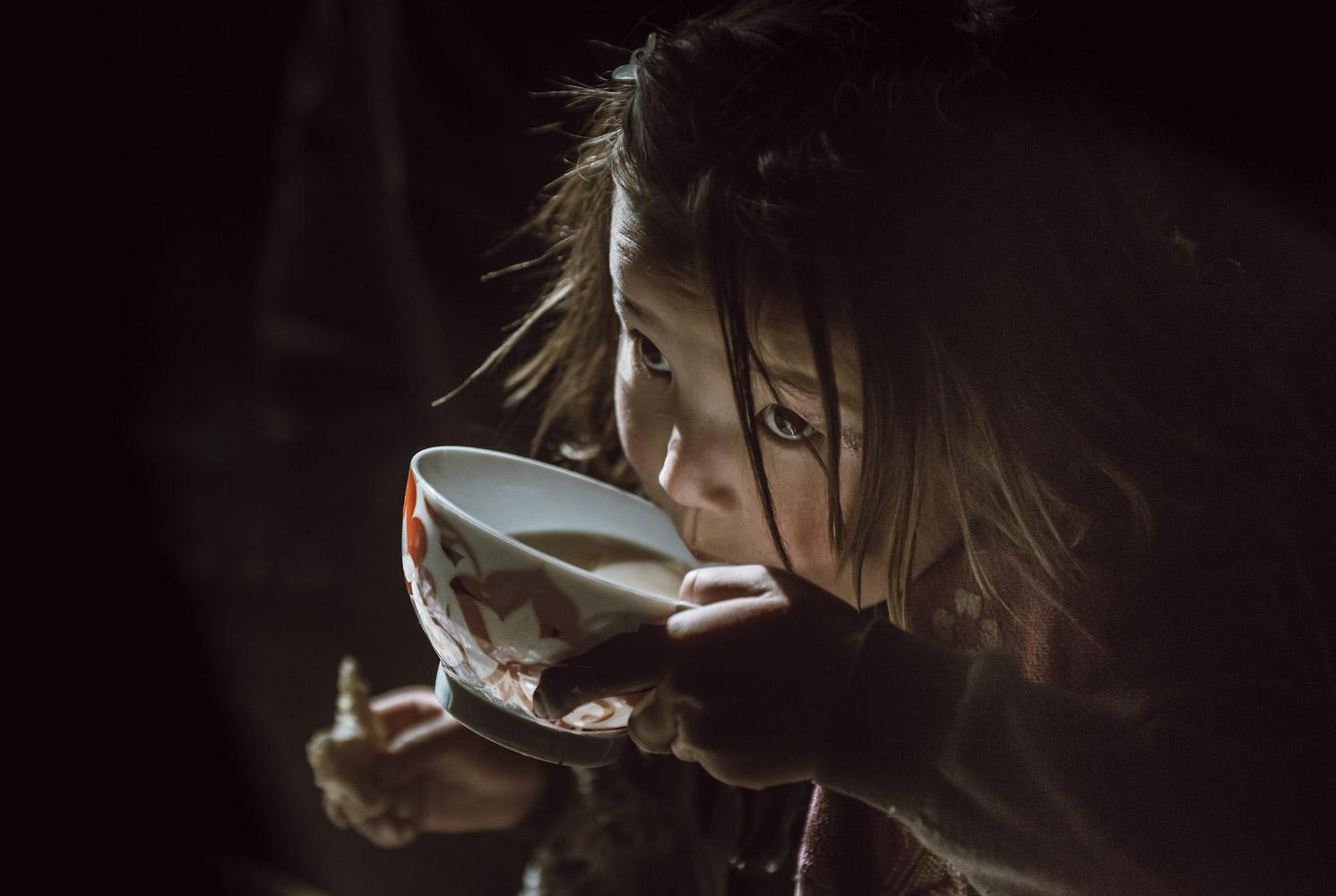 Казахская девушка пьет свой утренний чай, © Атул Прасад, Сан-Диего, США, Первое место в категории «Любитель: Младенцы / Дети», Конкурс портретной фотографии «Лица»